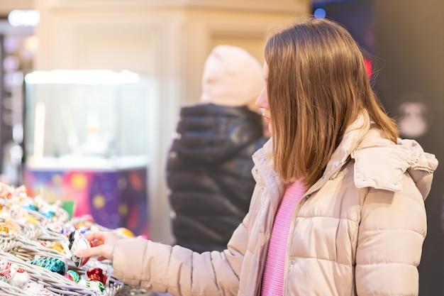 Nieuwjaar winkelen. jong meisje kiest geschenken, souvenirs op de kerstmarkt