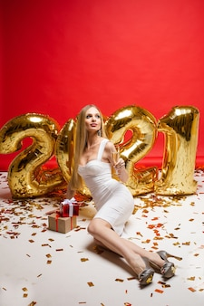 Nieuwjaar xmas vieren concept. mooie vrouw, ballonnen in de vorm van 2021, geschenken, gouden confetti op rode muur.