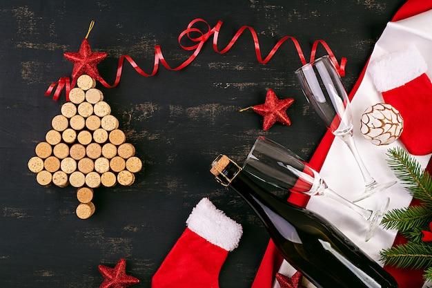 Nieuwjaardecoratie met kerstboom gemaakt van wijnkurken en een fles champagne. kerst achtergrond. bovenaanzicht