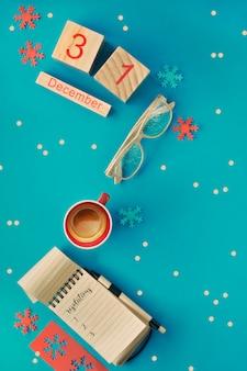 Nieuwjaarresoluties - notitieboekje, glazen, houten kalender en koffie op blauw