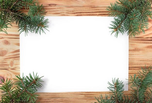 Nieuwjaars- en kerstkaart op een houten ondergrond met dennentakken, plat gelegd, kopieerruimte, mock-up.