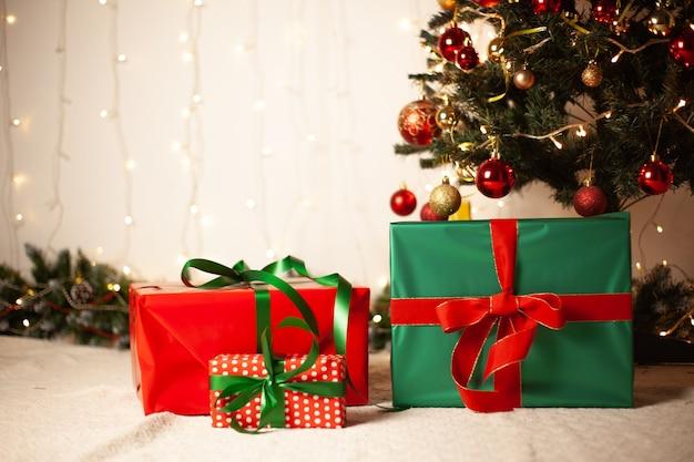 Nieuwjaars, kerstcadeaus liggen onder de kerstboom. rode en groene geschenkdozen. aanwezig, geschenken.
