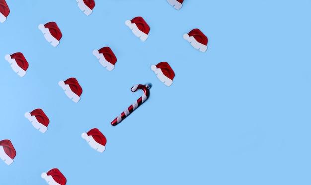 Nieuwjaars patroon, kleine hoedjes van de kerstman liggen diagonaal op een blauwe achtergrond. het ritme wordt doorbroken door een speelgoedriet van een kerstboom. kopieer ruimte, plat leggen
