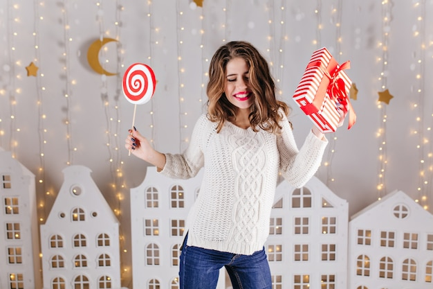 Nieuwjaars vakantiefoto van jonge, grappige vrouw in zachte gebreide trui en spijkerbroek, dansen met cadeau in haar linkerhand en grote snoep in haar rechterhand