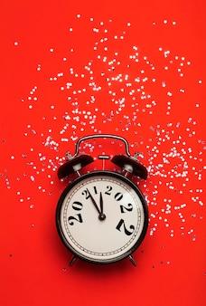 Nieuwjaarsachtergrondconcept verandert in op een wekker op een rode achtergrond met feestelijke glitter...