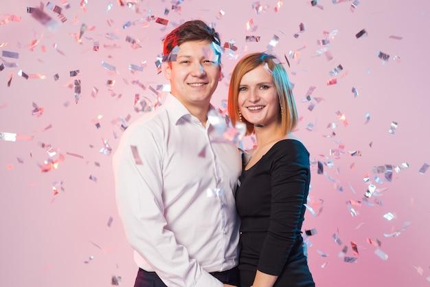 Nieuwjaarsavond feest. vrolijke vreugdevolle jong koppel permanent met dalende confetti