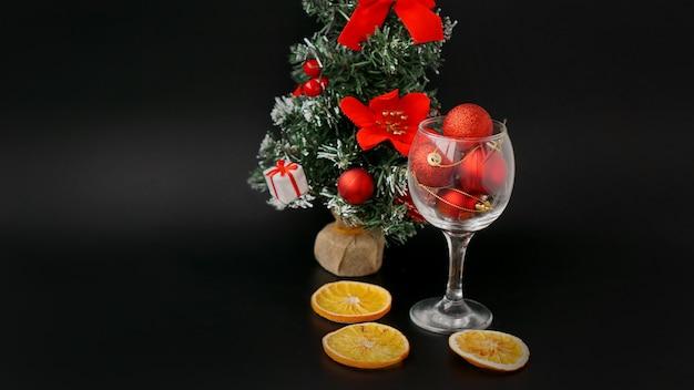 Nieuwjaarsboom op een zwarte achtergrond. rode kerstballen in een wijnglas, decor van droge sinaasappels
