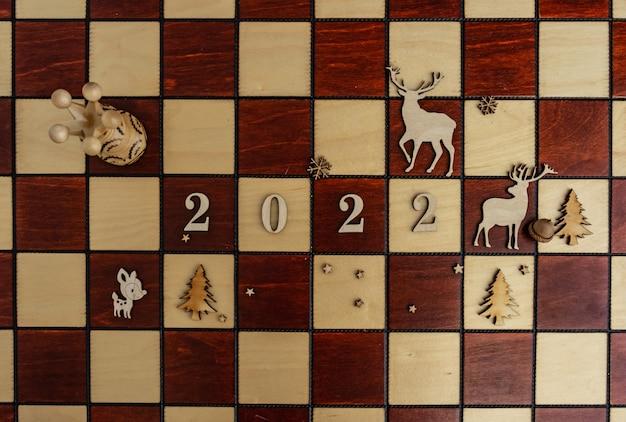 Nieuwjaarscompositie op een schaakbord met een koningin en andere stukken 2022 platliggend bovenaanzicht