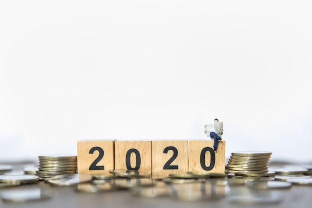 Nieuwjaarsconcept 2020, geld en planning. sluit van zakenmanminiatuur lezen een krant o