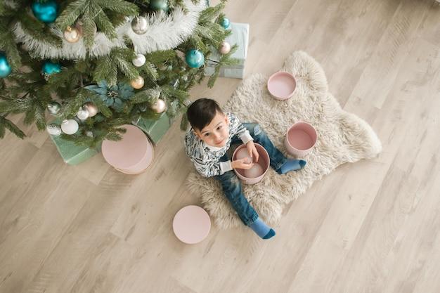 Nieuwjaarsconcept, een jongen in de buurt van een kerstboom