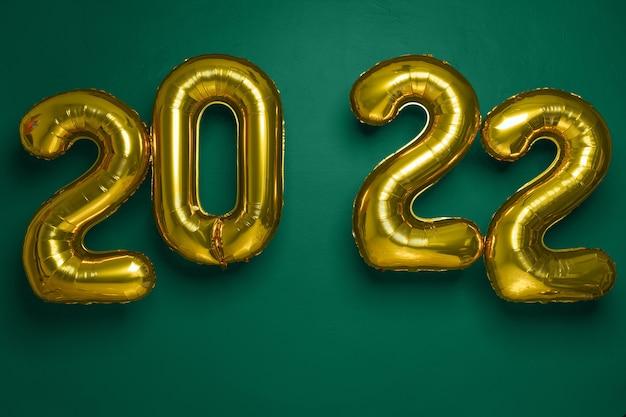 Nieuwjaarsconcept. gouden partij ballonnen 2022 nummers vorm op groene achtergrond, panorama, vrije ruimte.