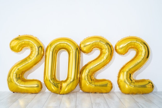 Nieuwjaarsconcept. gouden partij ballonnen 2022 nummers vorm op witte achtergrond, panorama, vrije ruimte. hoge kwaliteit foto