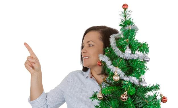 Nieuwjaarsconcept. mooie vrouw houdt versierde kerstboom vast en wijst met haar vinger om ruimte voor jeugdontwerp op een witte achtergrond te kopiëren