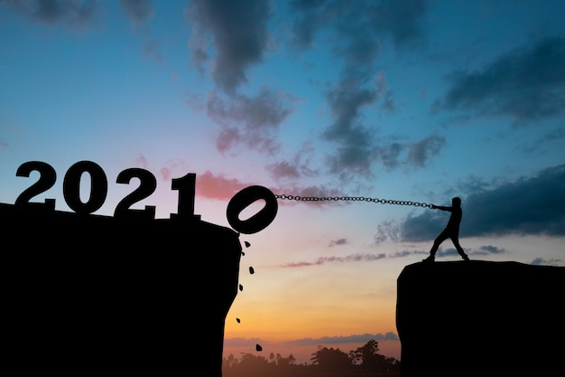 Nieuwjaarsconcept, silhouet van man trekt nummer omlaag naar succes in 2021