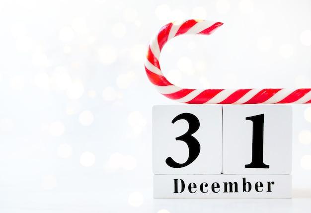 Nieuwjaarsdatum op kalender. houten kalender show van 31 december met rode en witte lolly
