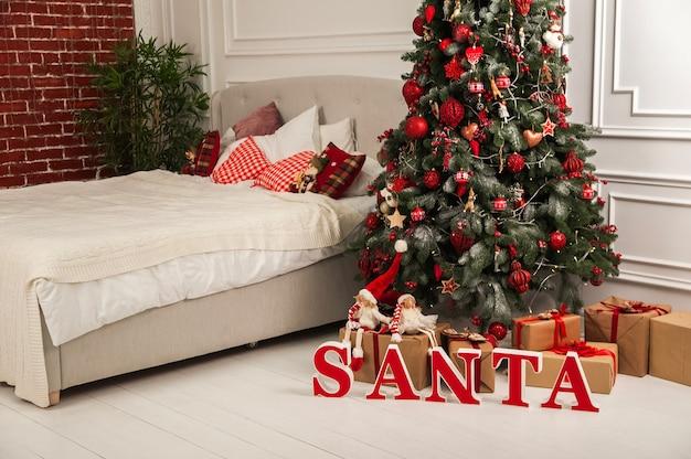 Nieuwjaarsdecor van de slaapkamer in de scandinavische stijl kerstboom kerstman en bed met kussens hygge nieuwjaarsconcept selectieve aandacht