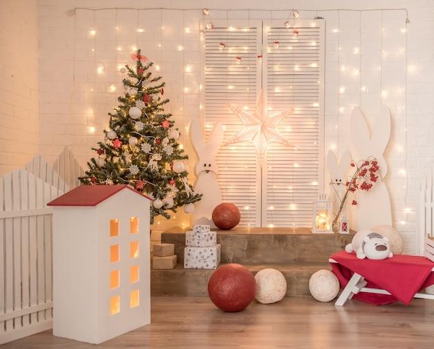 Nieuwjaarsdecor voor kinderen in de studio. op een witte bakstenen muur zijn er lichten, hazen, een boom, rode ballen.