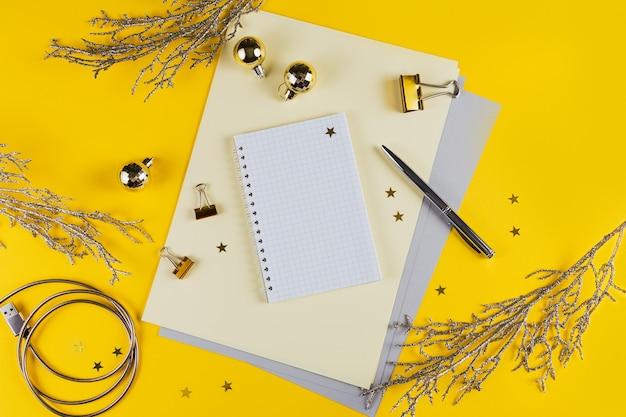 Nieuwjaarsdecoratie van gele bureaulijst met leeg notitieboekje en andere bureaulevering. bovenaanzicht met kopie ruimte, plat leggen.