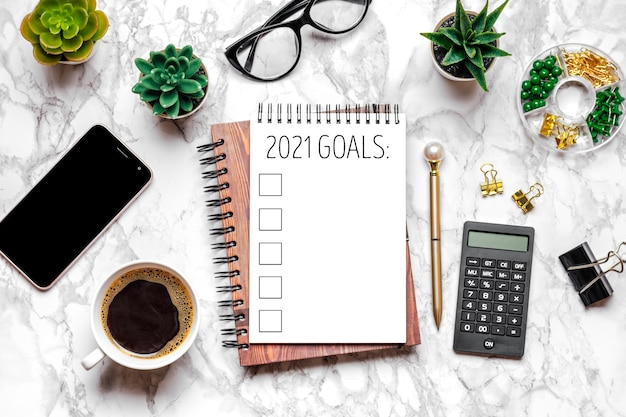 Nieuwjaarsdoel 2021, plan, actietekst op open blocnote, bril, kopje koffie, pen, smartphone