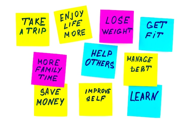 Nieuwjaarsdoelen of resoluties - kleurrijke plaknotities op een witte achtergrond.