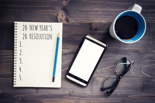 Nieuwjaarsdoelen, resolutie of actieplan 2020. kantoor houten tafel met lege kladblok, potlood, glazen, telefoon en kopje koffie.