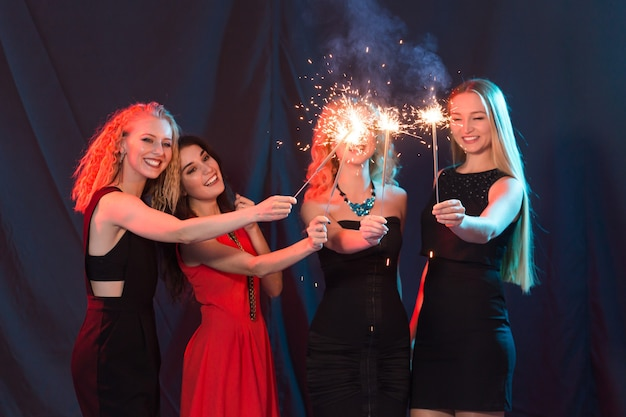 Nieuwjaarsfeest, feest en vakantieconcept - jonge vrolijke vrouwen met brandende sterretjes.