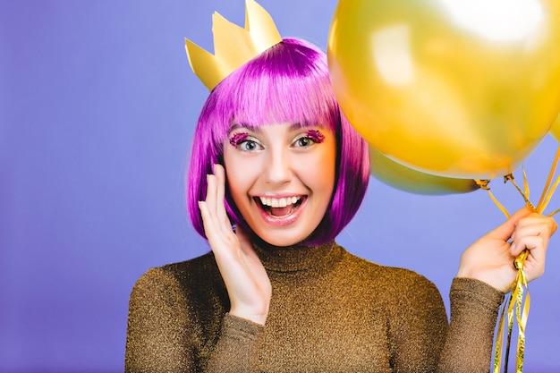 Nieuwjaarsfeeststemming van mooie grappige jonge vrouw met gouden ballonnen. knip paars haar, kroon, luxe jurk, heldere emoties, uiting van positiviteit, feest.