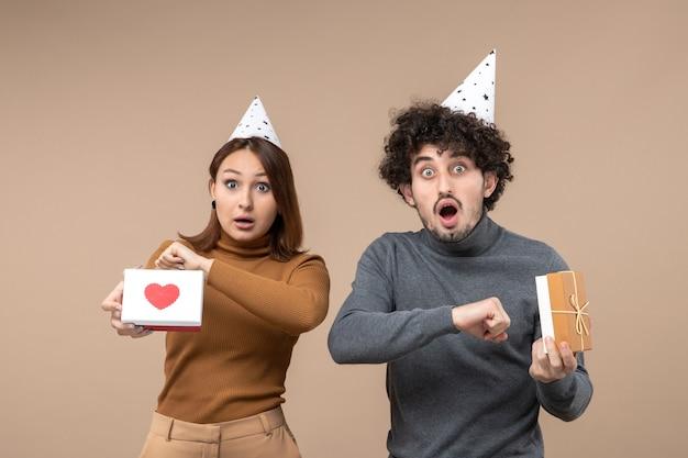 Nieuwjaarsfoto's met emotioneel verward jong stel dat hun tijd controleert, draagt nieuwjaarshoedmeisje