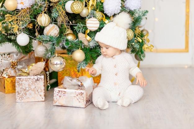 Nieuwjaarsfoto van de baby bij de kerstboom met een cadeau