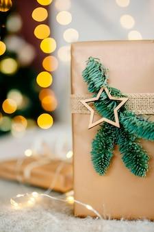 Nieuwjaarsgeschenk ligt op de achtergrond van lichten onder de boom. nieuwjaar en kerstmis. verpakte geschenken