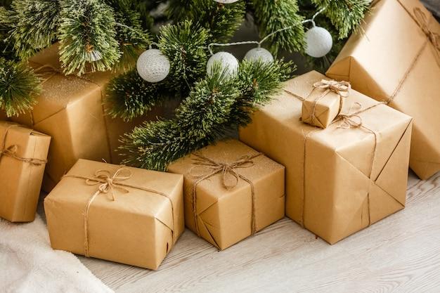 Nieuwjaarsgeschenken onder de kerstboom. de geschenken zijn verpakt in kraftpapier en vastgebonden
