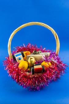 Nieuwjaarsgeschenken voor kinderen versierd met rood klatergoud in een mand.