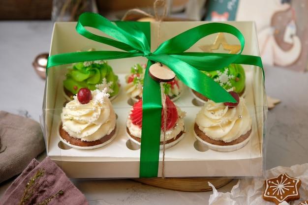 Nieuwjaarsgeschenksets met snoep. een doos cupcakes als kerstcadeau. taarten met cream cheese cream en pinda-karamel vulling.