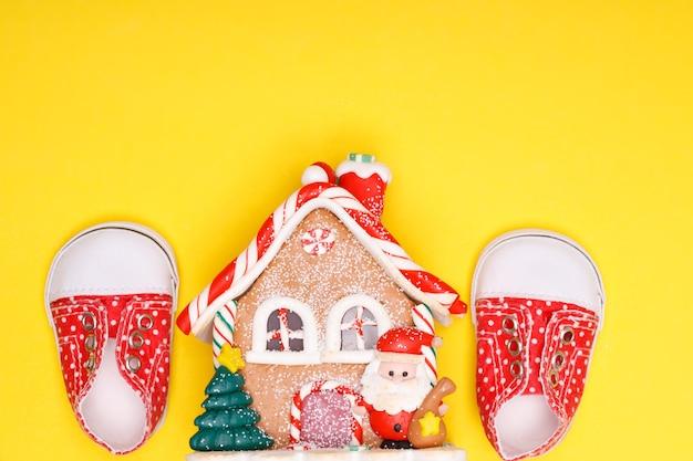 Nieuwjaarshuis met kinderschoenen van rode kleur met witte stippen op een gele achtergrond