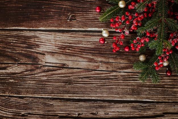 Nieuwjaarsjabloon met kerstboomversieringen, ballen en rode bessen op een houten gestructureerd oppervlak. uitzicht van boven.
