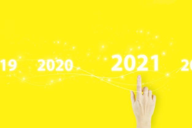 Nieuwjaarskaart bedrijfsconcept. jonge vrouw hand wijzende vinger met hologram 2021 teken op gele achtergrond.