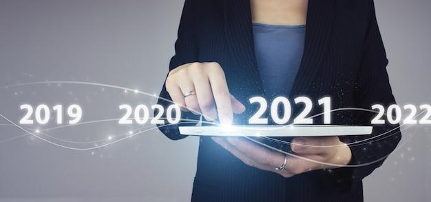 Nieuwjaarskaart bedrijfsconcept. witte tablet in zakenvrouw hand met digitaal hologram 2021 jaar teken op grijze achtergrond.
