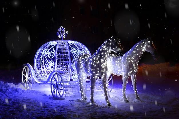 Nieuwjaarskaart. lichtgevende figuur van paarden met een rijtuig. sneeuw, nacht. plaats voor tekst
