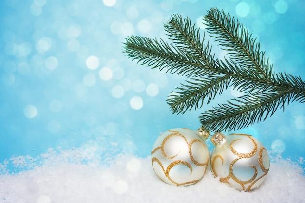 Nieuwjaarskaart met een twijg van een kerstboom en ballen op een blauw