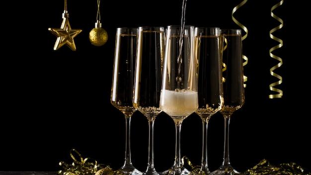 Nieuwjaarskaart voor het vullen van een glas wijn en decoratie in geel. een populaire alcoholische drank.