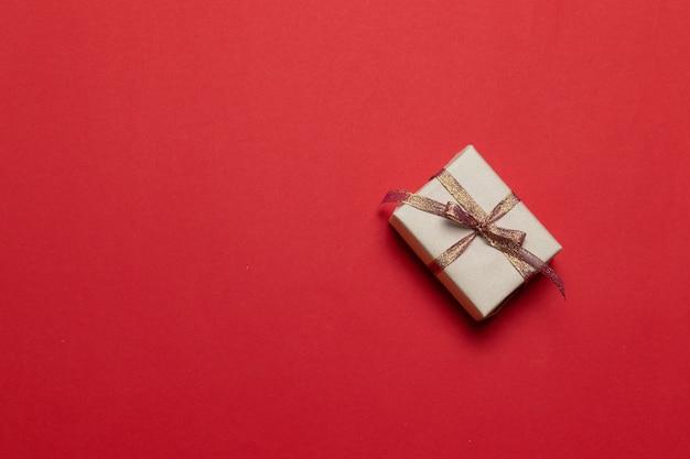 Nieuwjaarskerstverrassing aanwezig handgemaakte geschenkdoos op rode achtergrond. sjabloon wenskaart.