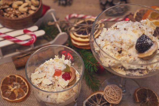 Nieuwjaarskerstversieringen met kerstboomversieringen en dessert zoet in glazen