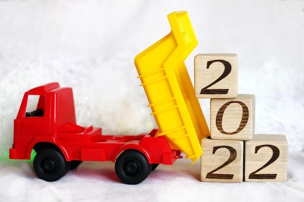 Nieuwjaarsnummer 2022 op houten blokken die worden gelost door een speelgoedkiepwagen op witte achtergrond. gelukkig nieuwjaar.
