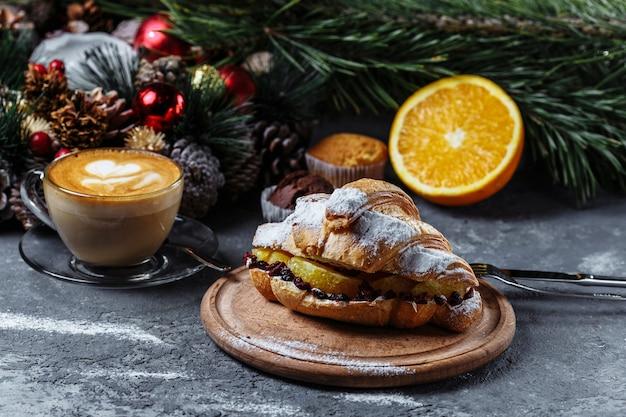 Nieuwjaarsontbijt met croissants. nieuwjaarscroissant met chocolade en gebakken sinaasappel.