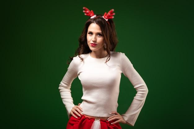 Nieuwjaarsportret van een jonge vrouw in een hertenrand en een witte trui die charmant glimlacht en poseren