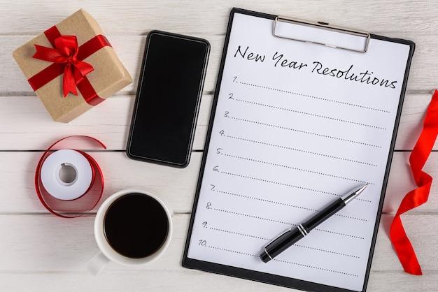 Nieuwjaarsresolutielijst geschreven op klembord met geschenkdoos en slimme telefoon, pen, koffie