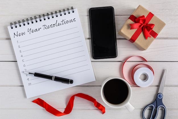 Nieuwjaarsresolutielijst geschreven op notebook met geschenkdoos en slimme telefoon, pen, koffie