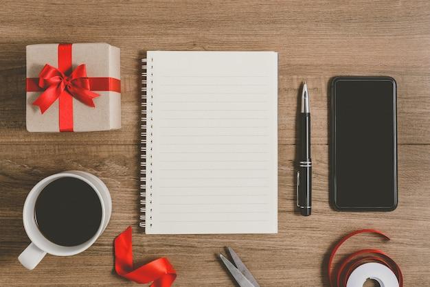 Nieuwjaarsresolutielijst geschreven op notebook met geschenkdoos en slimme telefoon
