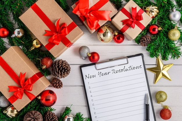 Nieuwjaarsresolutielijst geschreven op wit papier op klembord met kerstmisspar en decoratie