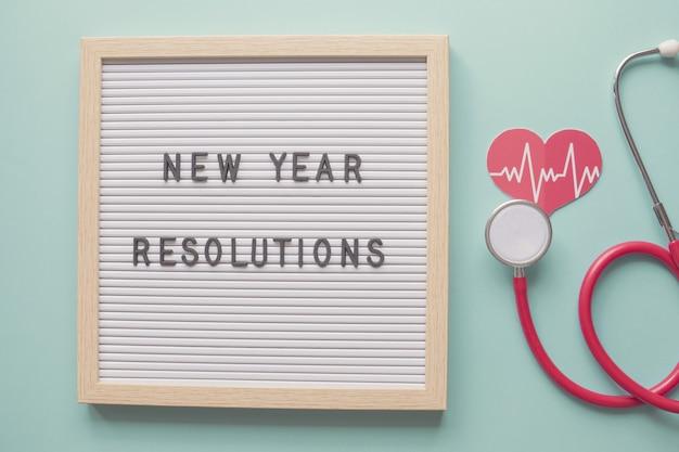 Nieuwjaarsresoluties op letterbord met hart en stethoscoop gezondheids- en welzijnsconcept